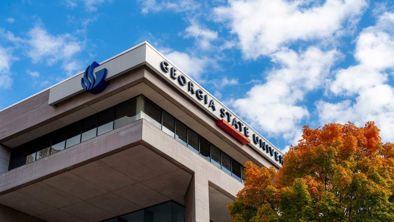 Top of building with Georgia State logo and sky above and tree to right