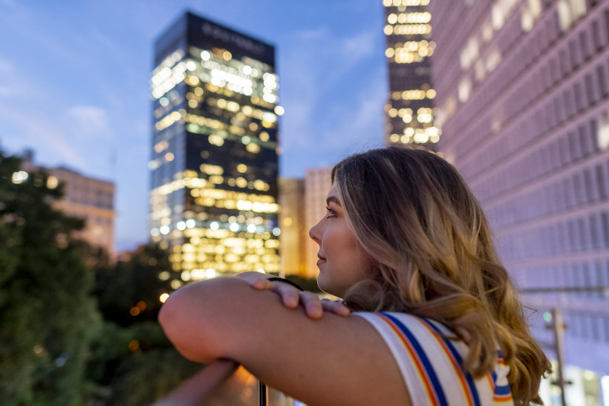 upper body side shot of female student with night skyline of Atlanta in background